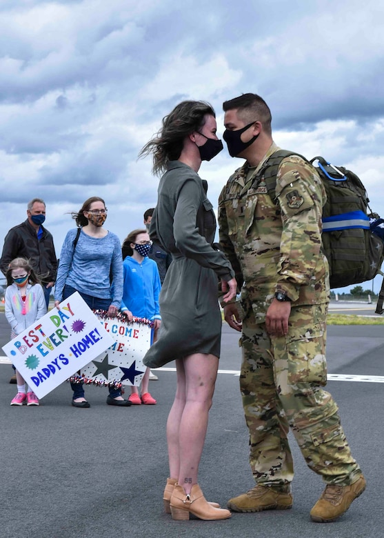 A 93rd Air Refueling Squadron member arrives from deployment and greets his loved one on Fairchild Air Force Base, Washington, July 1, 2020. Seventy-six members of the 93rd ARS deployed for seven months in support of Operation Inherent Resolve. (U.S. Air Force photo by Airman 1st Class Kiaundra Miller)