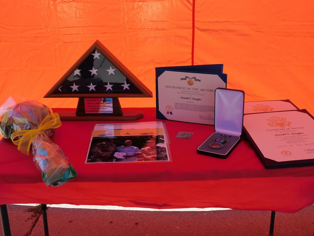 The certificates, award, flag, coin and pin presented to Donald F. Douglas sit upon a table at his retirement ceremony.