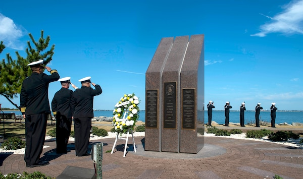 Sailors assigned to the Arleigh Burke-class guided missile-destroyer USS Cole (DDG 67) render honors at the USS Cole Memorial at Naval Station Norfolk during a commemoration of the Oct. 12, 2000 terrorist attack in Yemen that killed 17 Sailors.