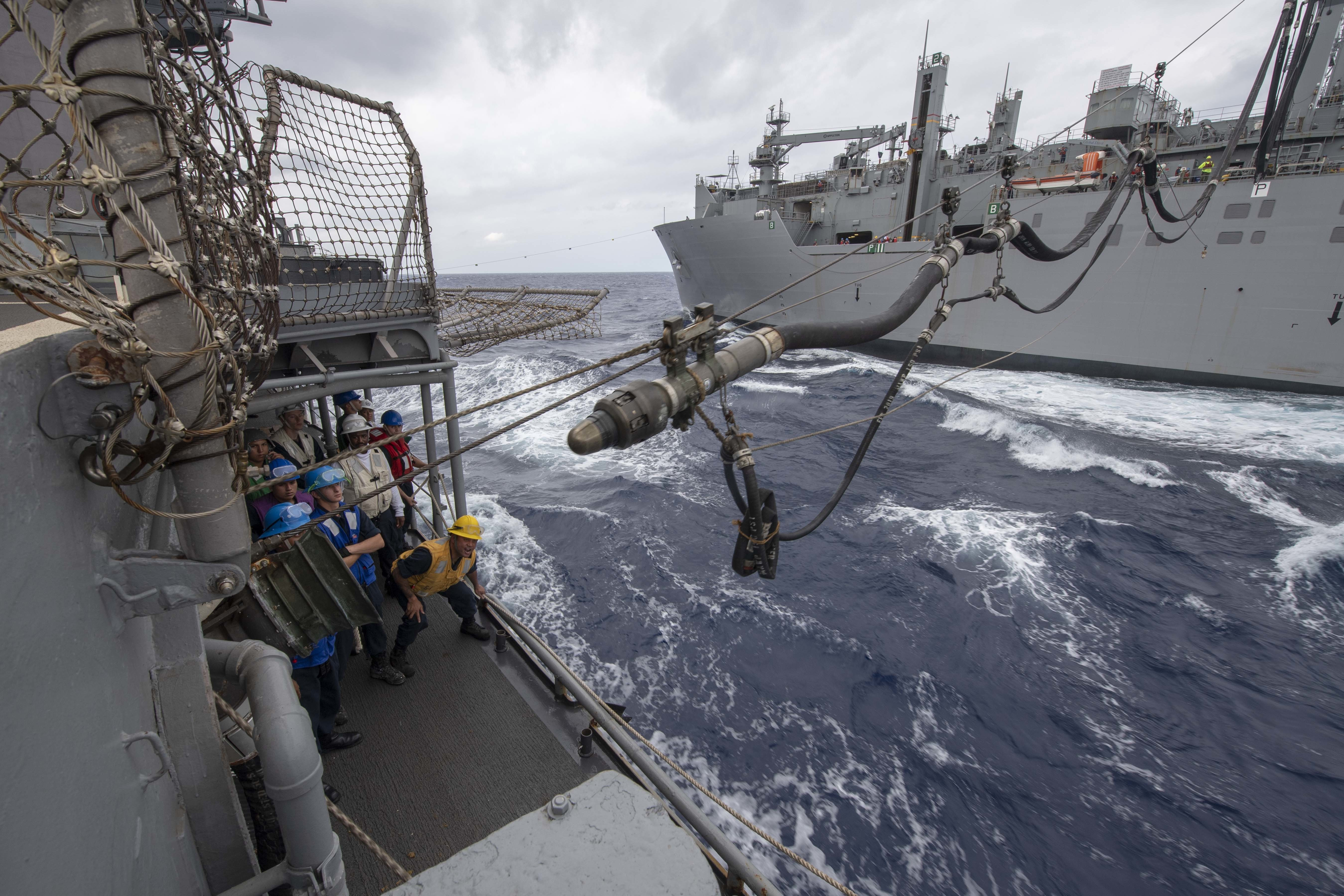 Sailors aboard the Ticonderoga-class guided-missile cruiser USS Antietam (CG 54) prepare to receive a fuel line during a replenishment-at-sea with the Lewis and Clark-class dry cargo ship USNS Carl Brashear (T-AKE 7)