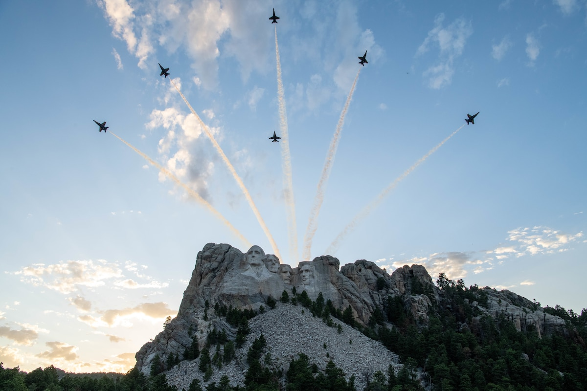 Six military aircraft fly over Mount Rushmore.