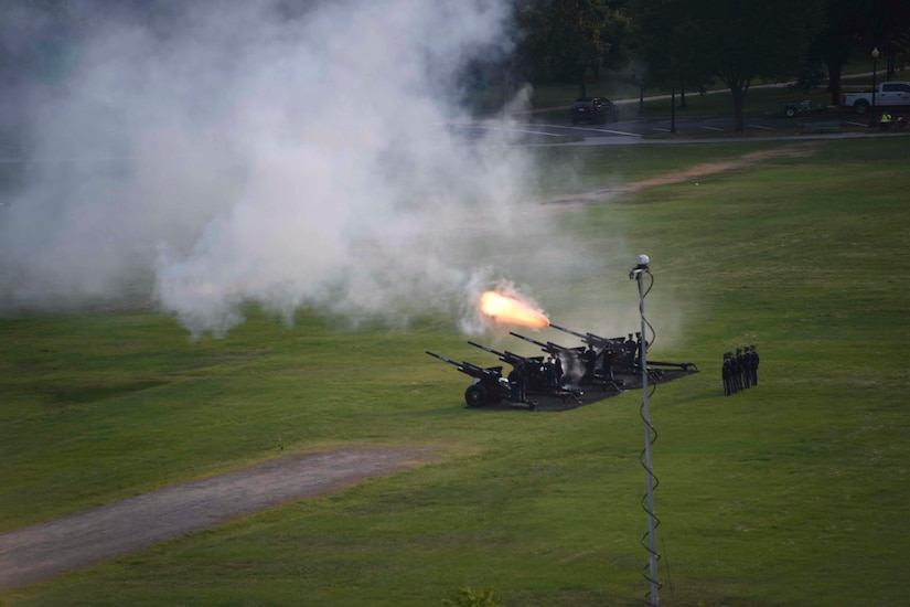 Military service members fire a cannon on a large lawn.