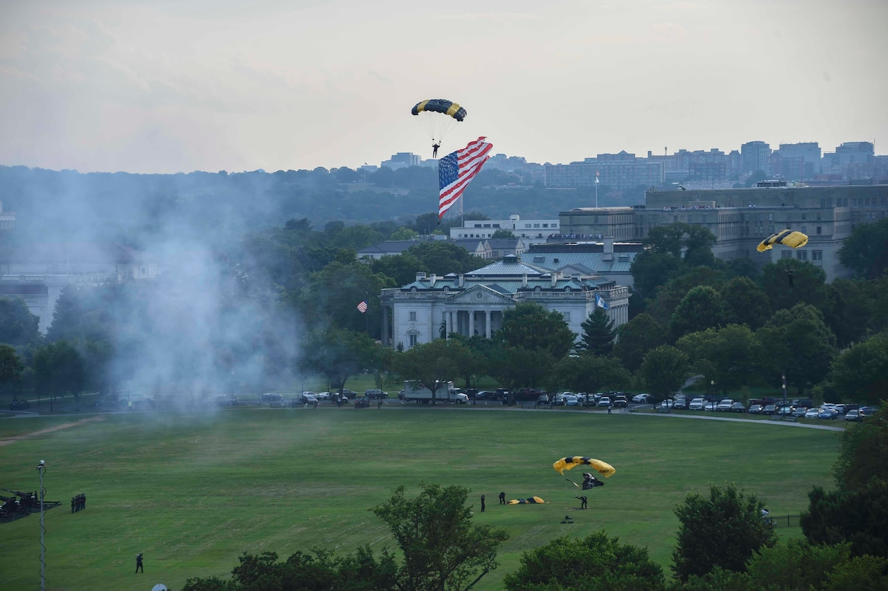 A parachutist carrying an American flag descends near the White House.