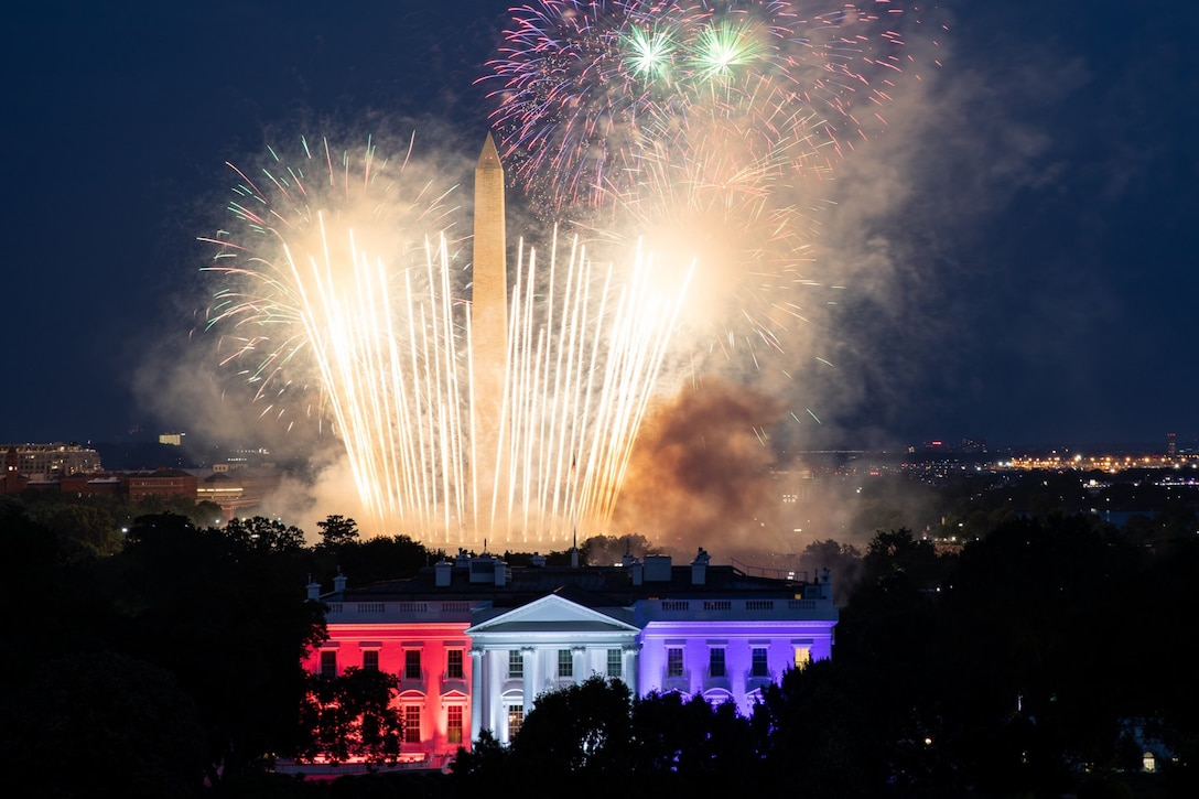 Fireworks illuminate the night sky over the White House and the Washington Monument.