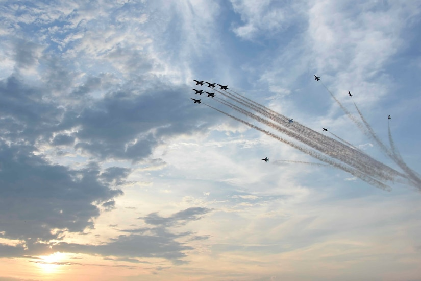 Military aircraft fly through a cloudy sky at dusk.