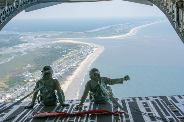 Senior Airman Gage Stevens (Left) and Master Sgt. Jim Ebert (Right), both loadmasters, Team Charleston, Joint Base Charleston, S.C. wave to beachgoers down the coast of South Carolina July 4, 2020 from inside a C-17 Globemaster III. The flight was in part to Salute from the Shore.