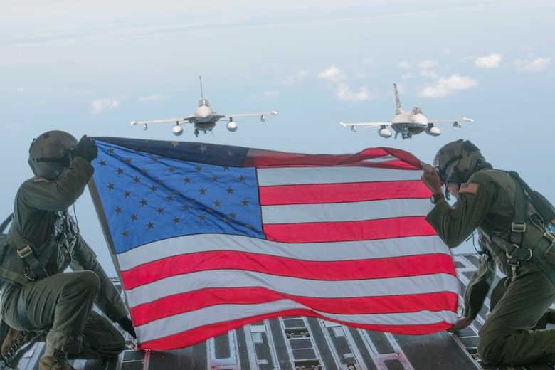 Members of Team Charleston hold the flag up in honor of fallen Air Force Hero 1st Lt. David Schmitz, pilot, 77th Fighter Squadron, Shaw Air Force Base on July 4, 2020 at Joint Base Charleston, S.C. Two F-16 Fighting Falcons from The 169th Fighter Wing, McEntire Joint National Guard Base flew in formation behind the C-17 Globemaster III.