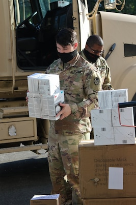 North Carolina Army National Guard Sgt. Brandon Eller, assigned to the 258th Engineer Battalion, loads personal protective equipment for delivery to public and charter school nurses in surrounding counties at a warehouse in Central N.C., June 29, 2020.