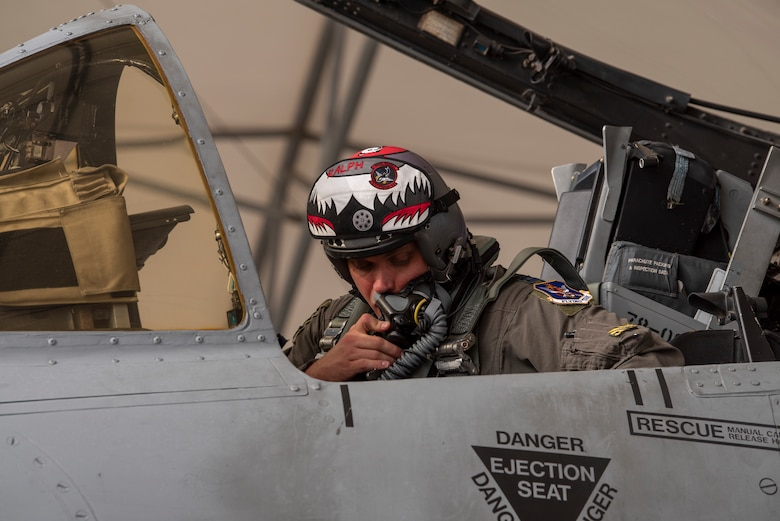 A photo of a pilot speaking into a helmet microphone