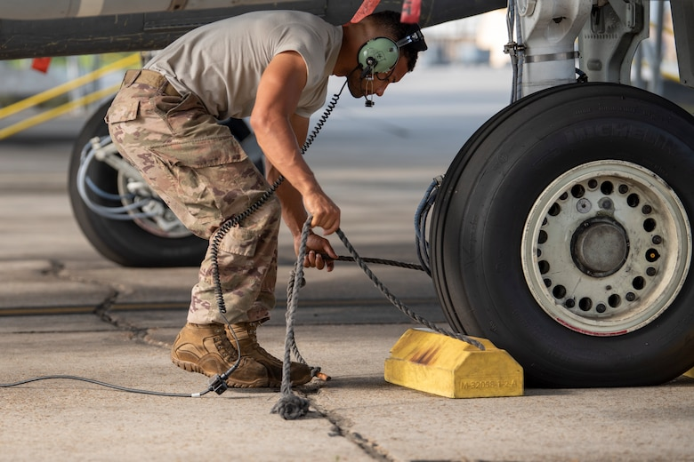 a photo of an airman pulling chalks from under an aircraft