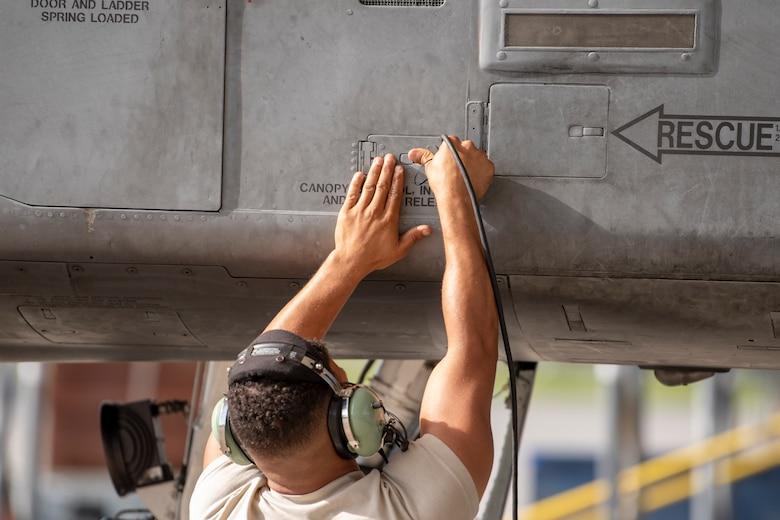 A photo of an Airman closing an aircraft panel