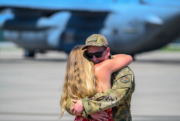 A member of the 130th Airlift Wing hugs a family member upon returning from an overseas deployment July 4, 2020, at McLaughlin Air National Guard Base in Charleston, W.Va. More than 70 members of the 130th Airlift Wing returned from Kuwait where they provided support for C-130H operations in the Middle East Area of Responsibility. (U.S. Air National Guard photo by Master Sgt. De-Juan Haley)
