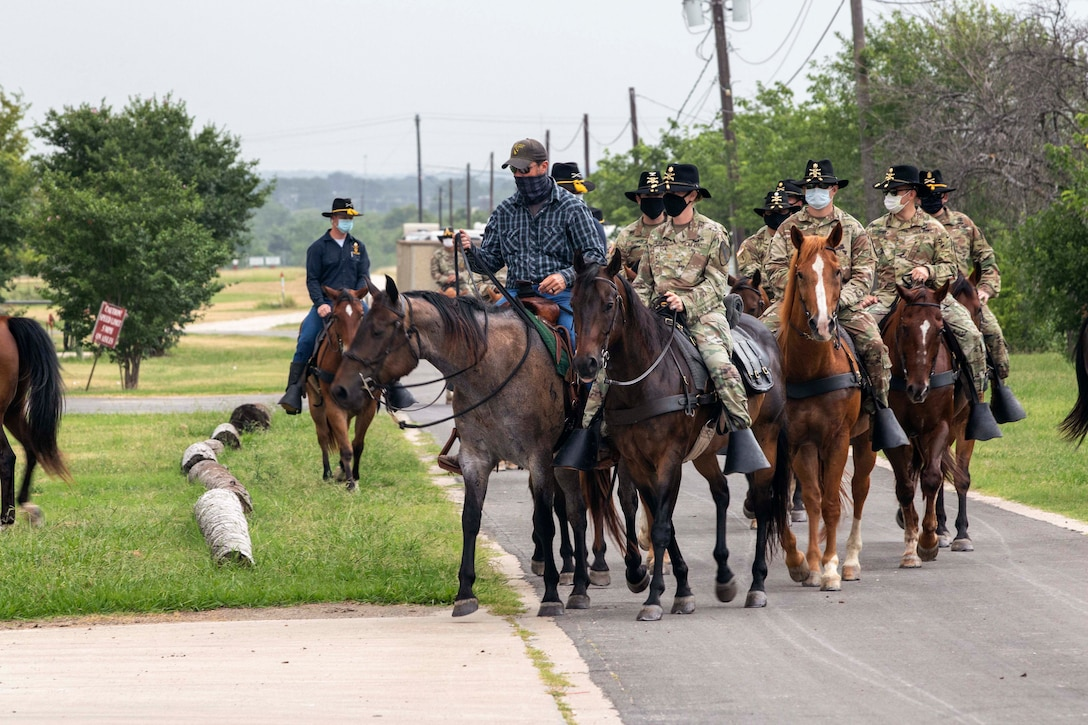 A group of soldiers ride horses.