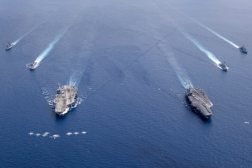 Military aircraft fly in formation over a group of military ships in the ocean.