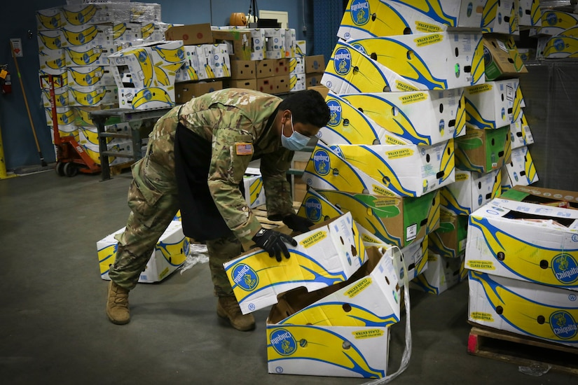 A soldier sorts cardboard boxes at a food bank.