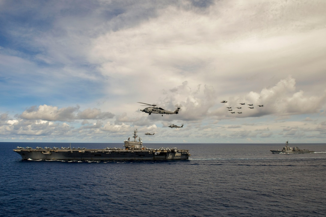 Aircraft fly over two ships in a body of water.