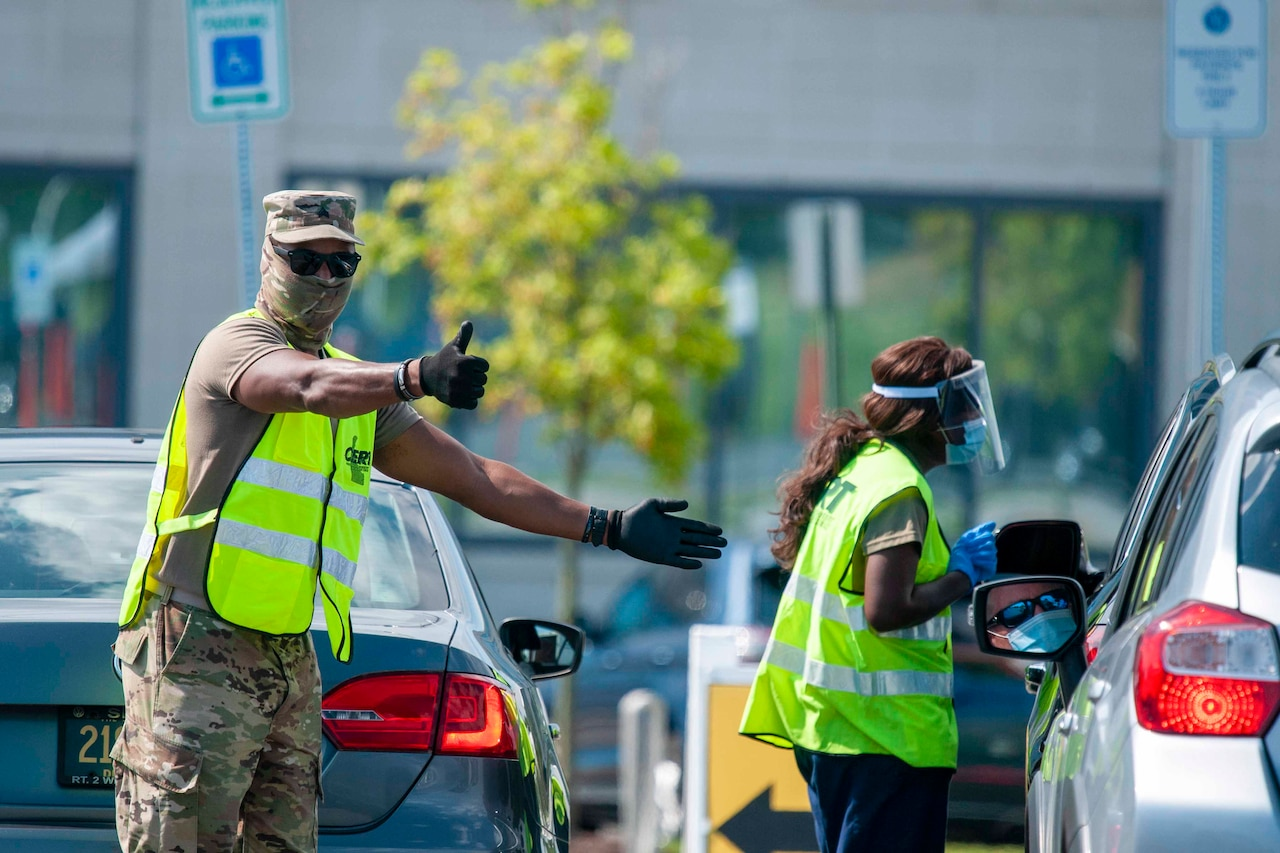 A soldier wearing personal protective equipment signals toward cars.