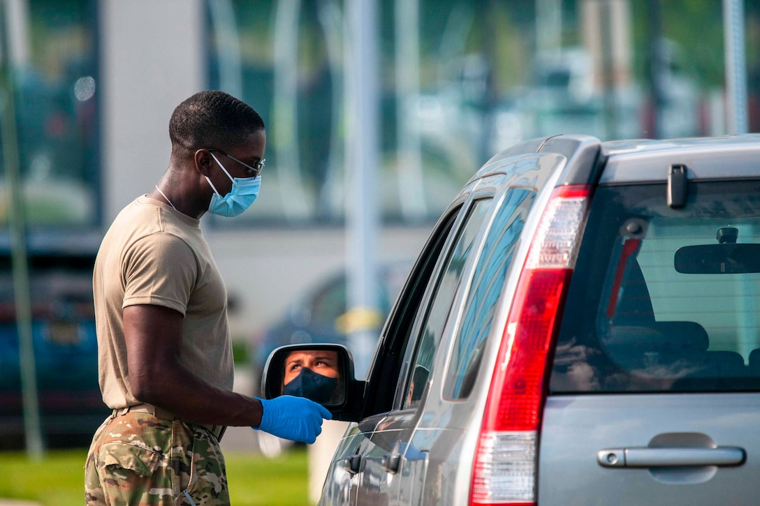 A soldier wearing personal protective equipment talks to a person sitting inside of a vehicle.