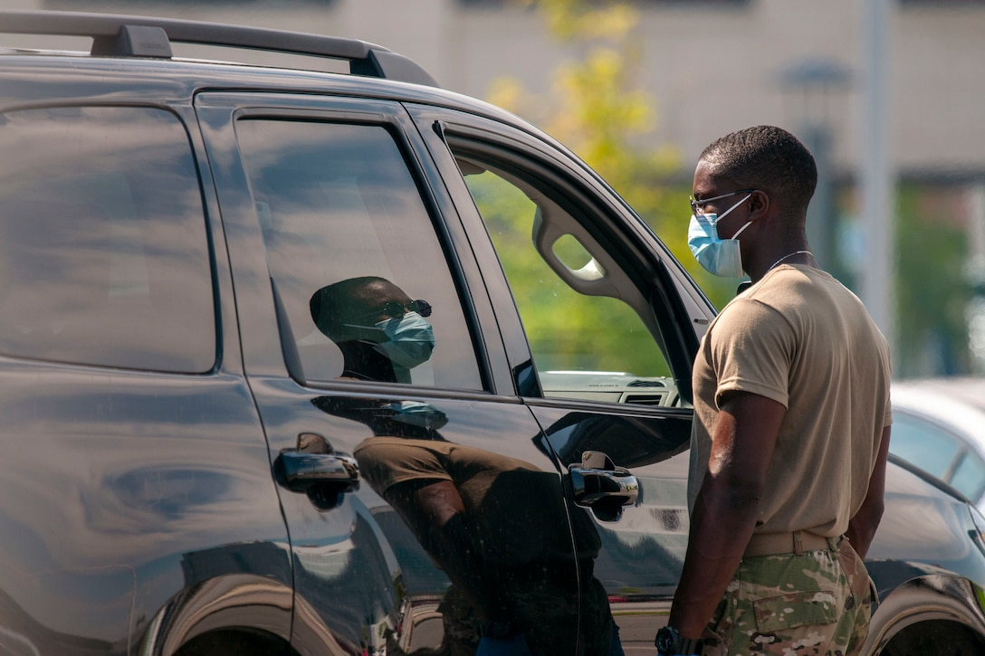 A soldier in protective gear stands on the passenger side of a car.