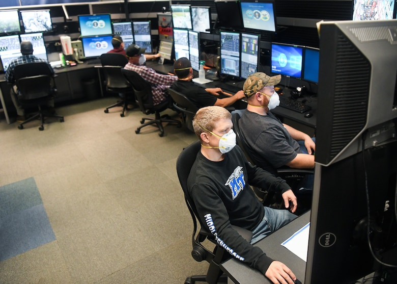 Adam Webb, bottom left, an electrical engineer, Justin Floyd, an outside machinist, and other Team AEDC personnel work in the control room of the Arnold Engineering Development Complex Aerodynamic and Propulsion Test Unit (APTU) May 20 while wearing masks to help mitigate risk associated with the coronavirus pandemic. The APTU team has performed their tasks, providing hypersonic testing capabilities, without interruption during the pandemic. Hypersonics is considered a critical field for national defense. (U.S. Air Force photo by Jill Pickett)