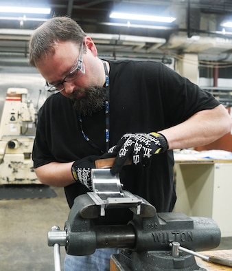Will Hale Jr., an inside machinist, uses a hone on the section of a test facility part to fine tune the fit of it to another section May 5 in the Model & Machine Shop at Arnold Air Force Base.