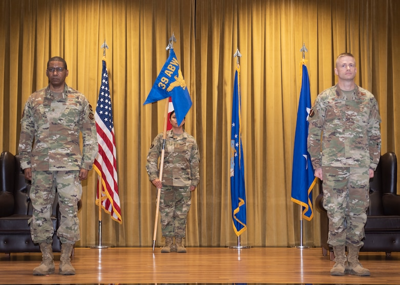 Photo of three Airmen standing on stage at a change of command