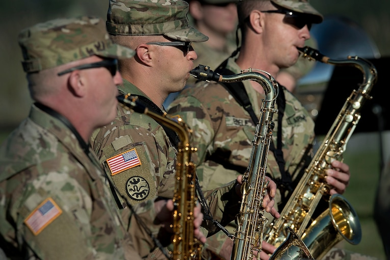 Three guardsmen play the saxophone next to one another.