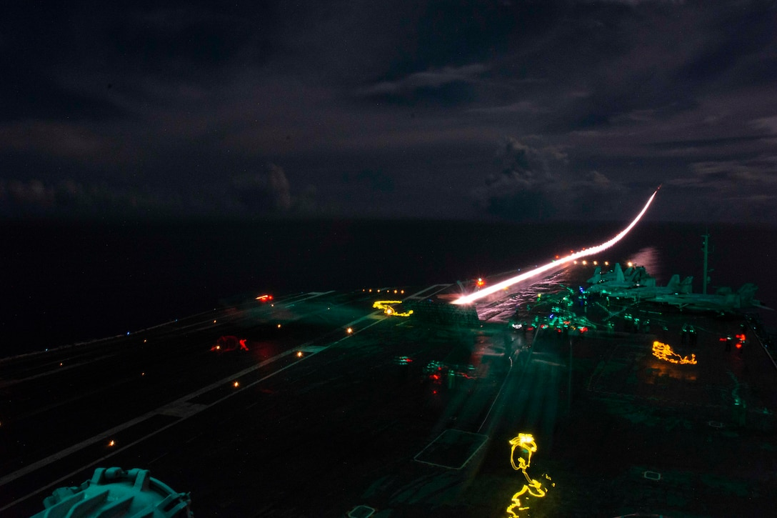 An aircraft launches from a ship illuminated by bright lights.