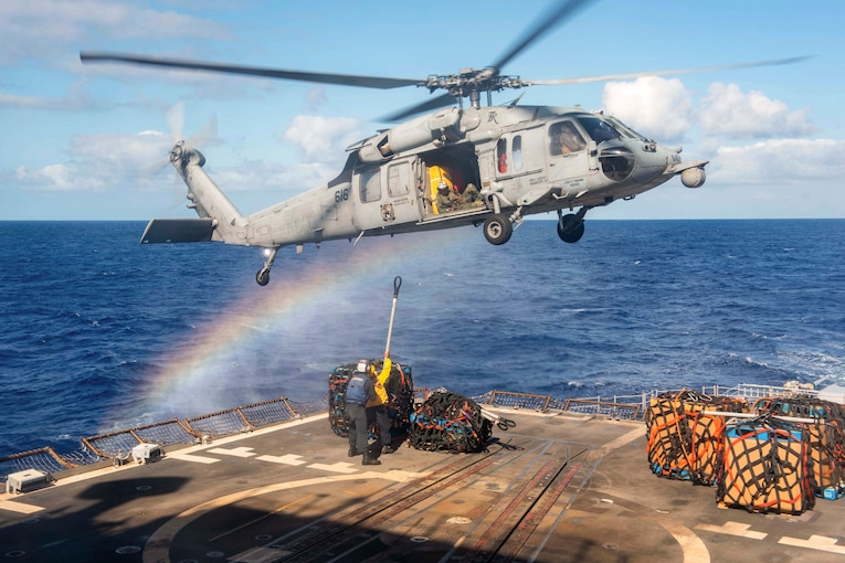 Two sailors attach cargo to a helicopter on a ship in the ocean.