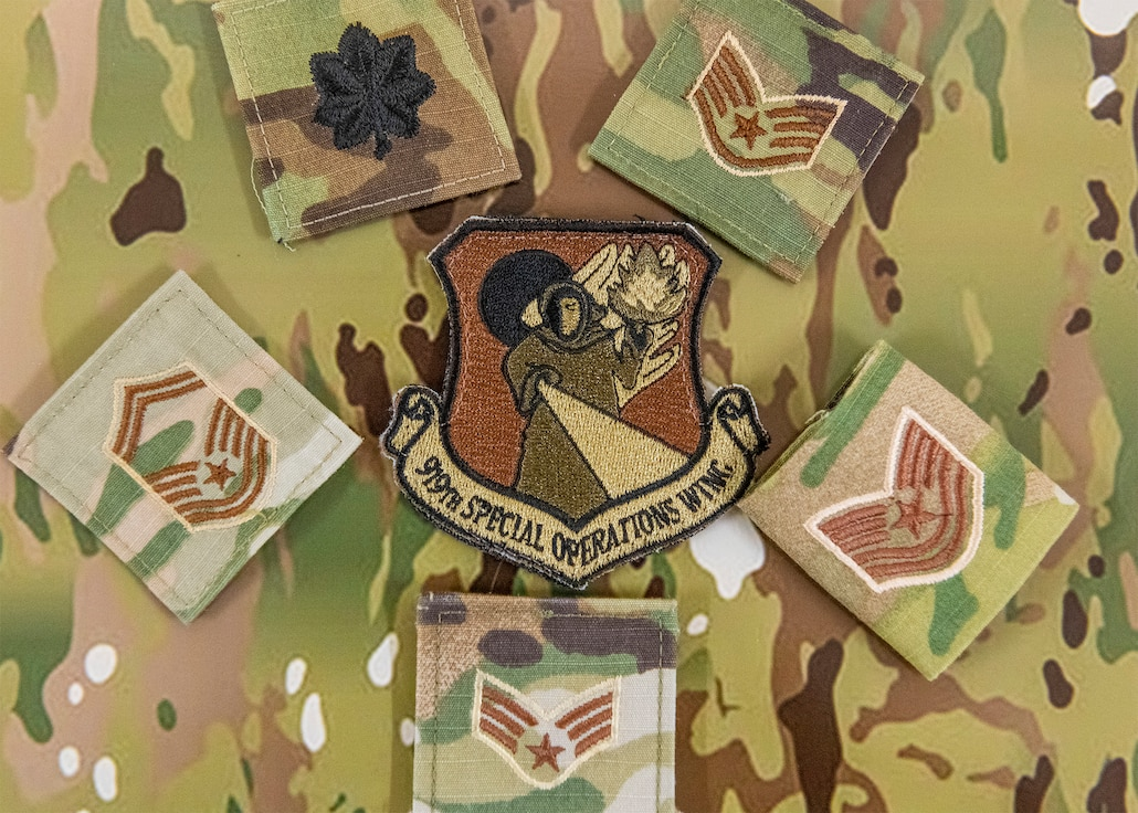 Uniform rank patches laying on camouflage pattern surrounding a 919th Special Operations Wing patch.