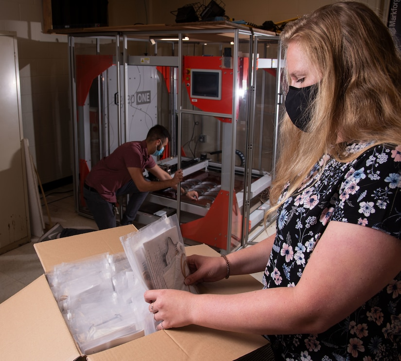 A woman wearing a mask places personal protective equipment into a plastic bag as a man in the background works at a 3D printer.
