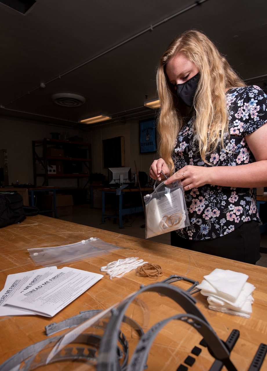 A woman wearing a mask puts 3D-printed personal protective equipment components into plastic bags.