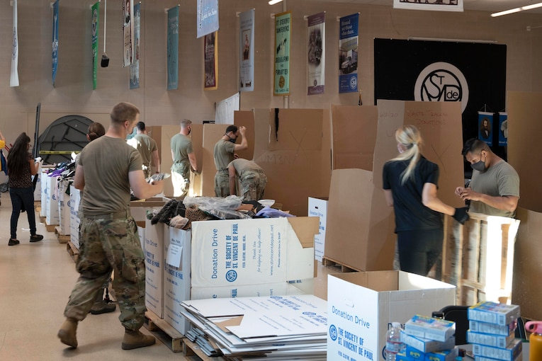 Guardsmen in protective gear sort through boxes.