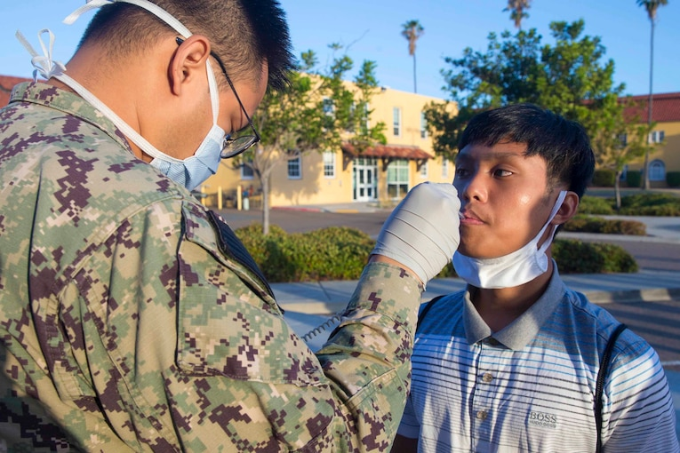 A Marine takes the temperature of a recruit using a thermometer.