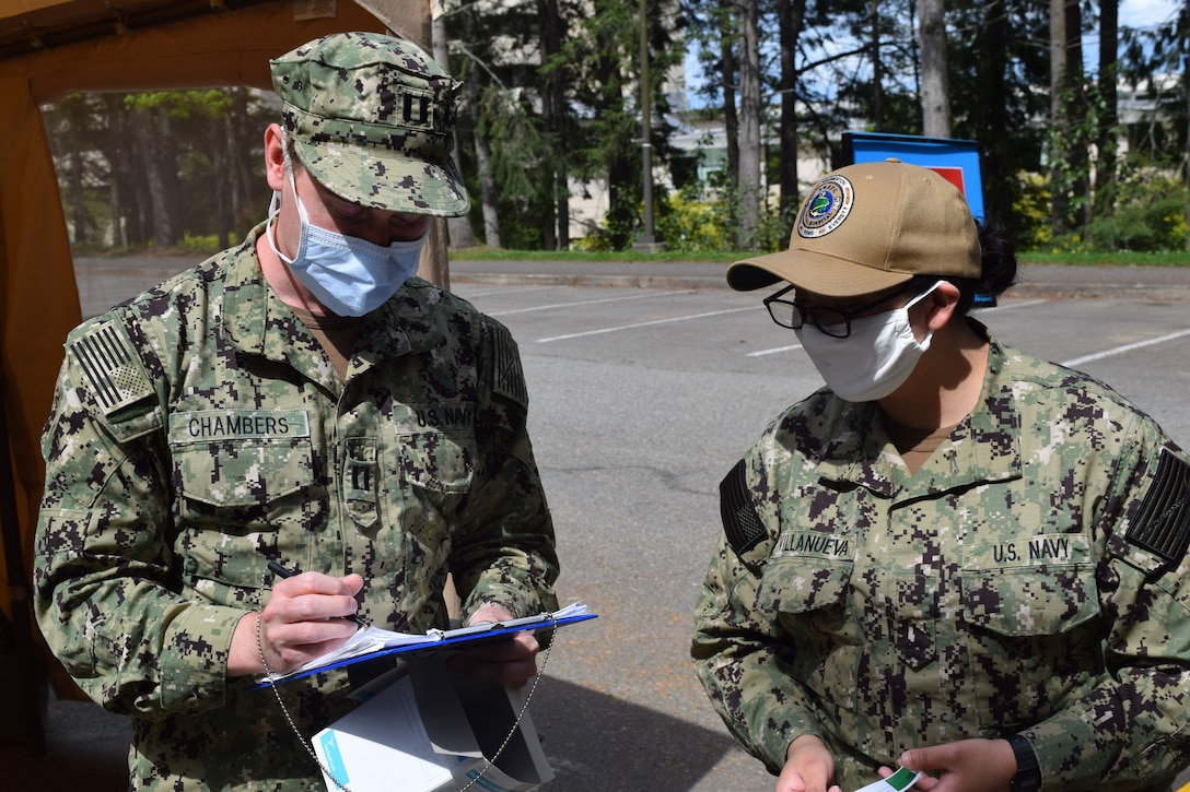 Two sailors wearing face masks and camouflage uniforms compare notes.