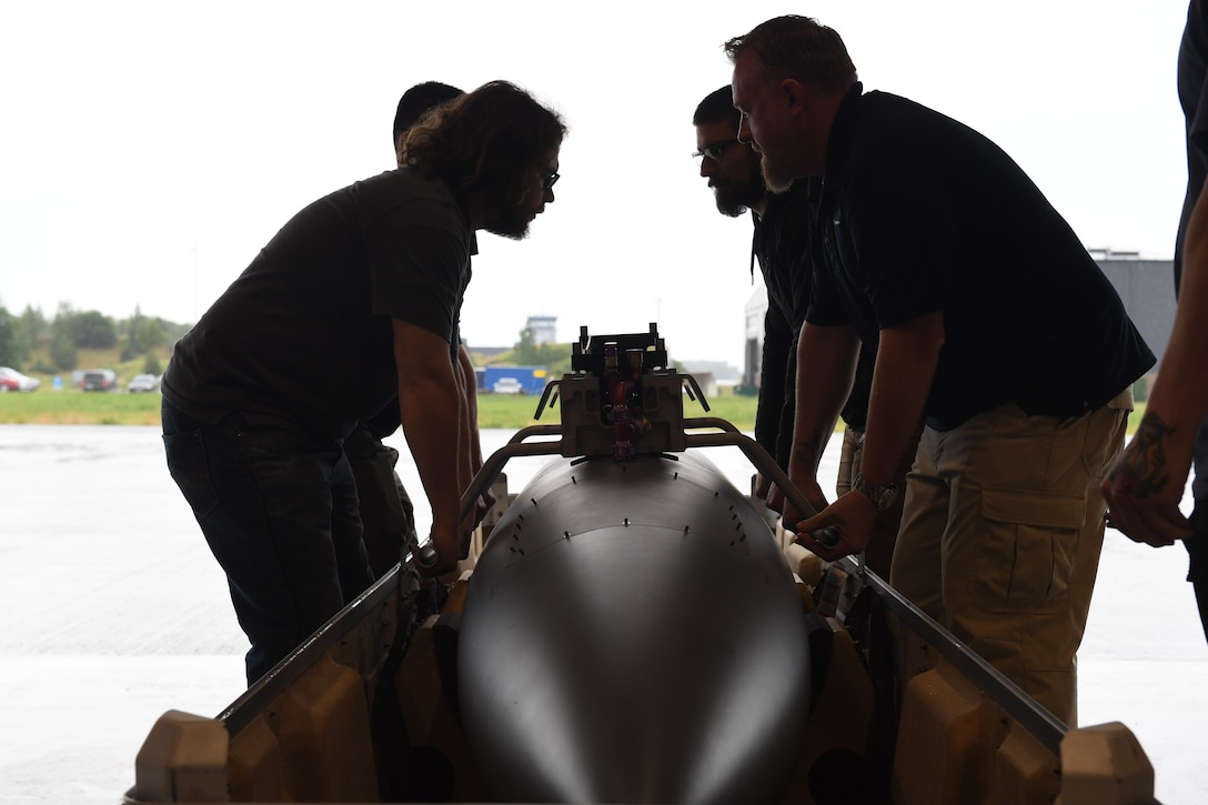 General Atomic aircraft maintenance technicians prepare to lift an MQ-9 Reaper fuel tank at Amari Air Base, Estonia, June 30, 2020. One of the aircraft was transported via cargo truck from Miroslawiec AB, where it was then offloaded and assembled in a hangar at Amari. (U.S. Air Force photo by Airman 1st Class Alison Stewart)