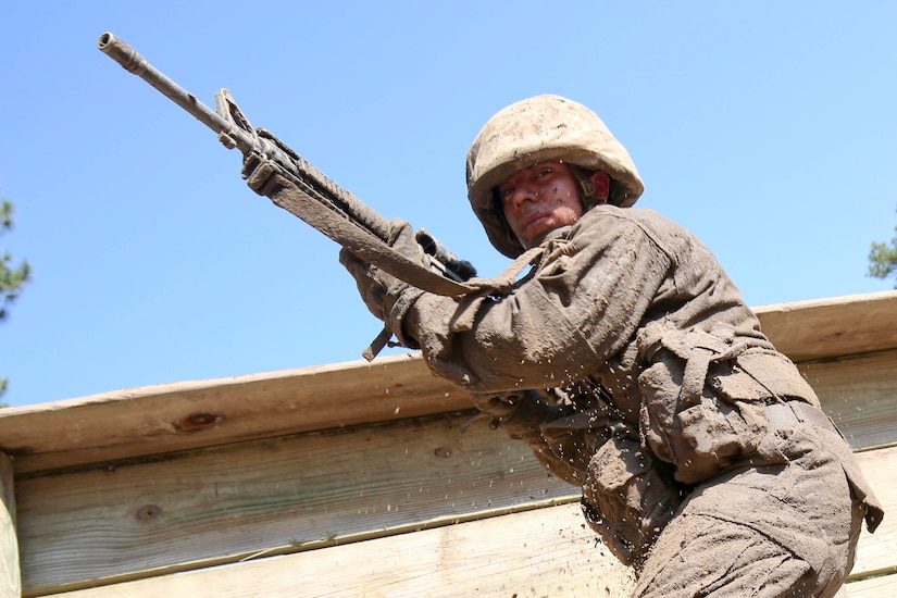 A Marine with a rifle. Part of an obstacle course is in the background.
