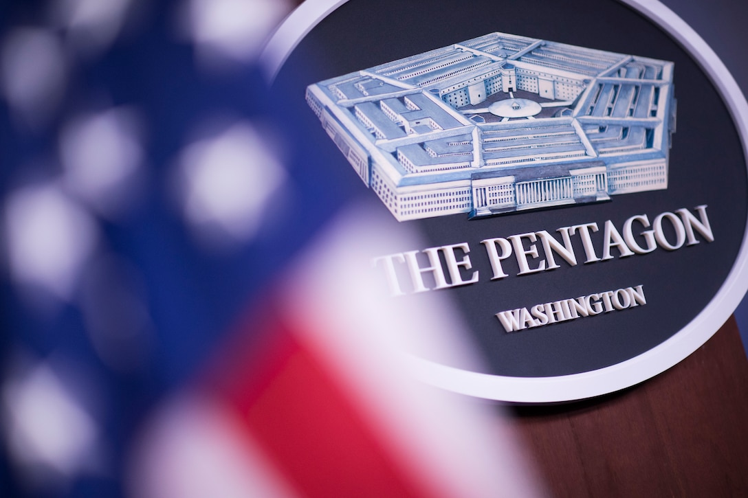 A sign that reads The Pentagon Washington sits behind the American flag.