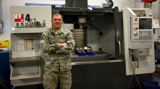 U.S. Air Force Staff Sgt. Alex Wynn, a machinist assigned to the Ohio National Guard's 180th Fighter Wing, poses in front of a Computer Numerical Control machine at the 180FW in Swanton, Ohio, March 8, 2020. Wynn used a similar machine and knowledge he learned at the 180FW to create a replacement gear for the Wood County Courthouse clock.