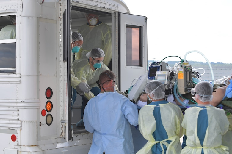 Medical personnel move a patient on a stretcher out of the back of a white bus.