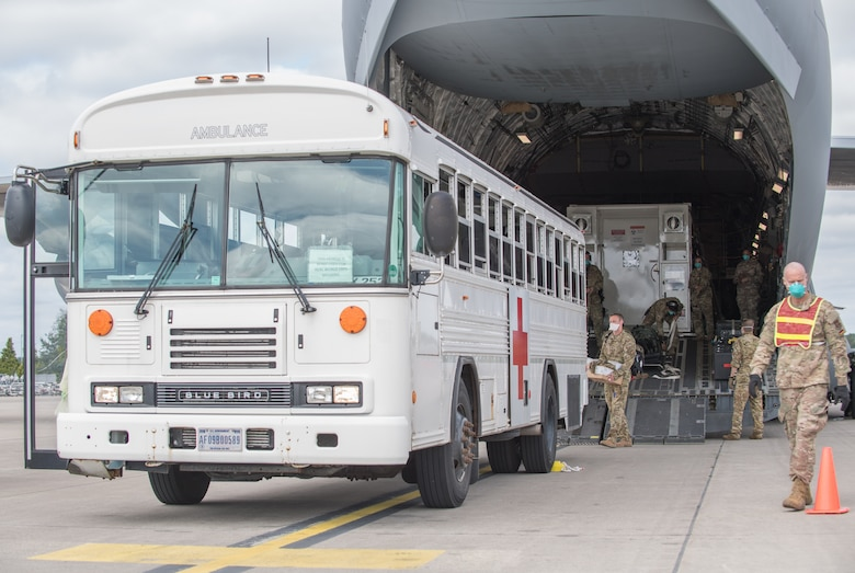 A white bus with a red cross on its side backs up to a large military aircraft.