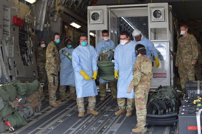 Medical personnel, some in military uniforms, gather outside a large metal box that is situated inside a large military aircraft.