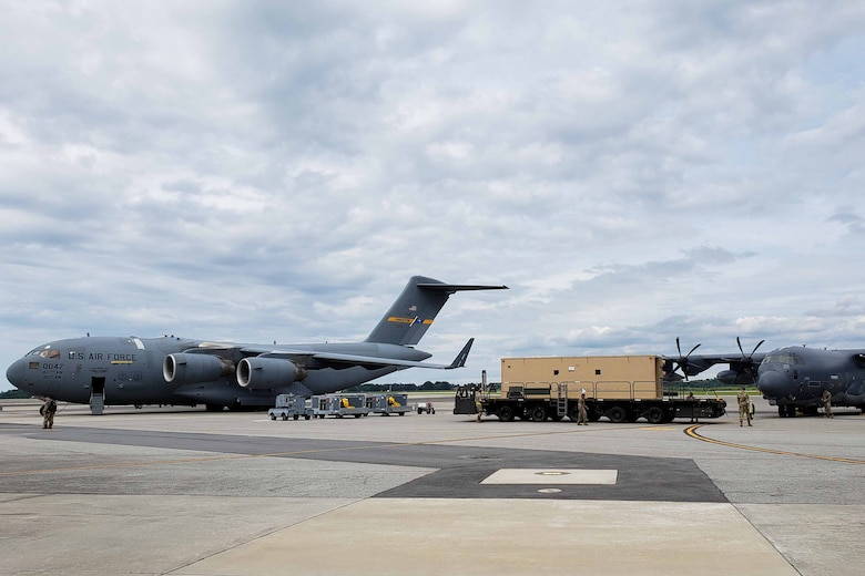 Two transport aircraft on a ramp with a large, multiwheeled flatbed vehicle between them.