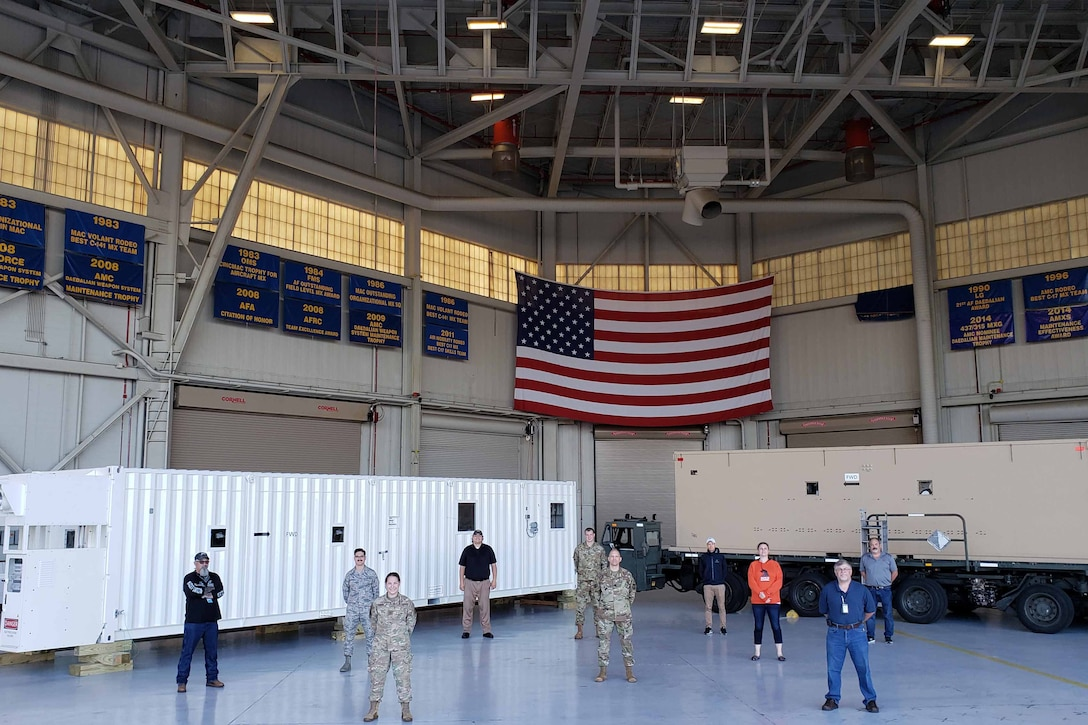 Airmen and civilians stand in a hangar beneath a large U.S. flag.