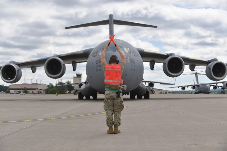 A service member stands on a flight line and uses orange-colored wands to direct the movement of a large military aircraft.