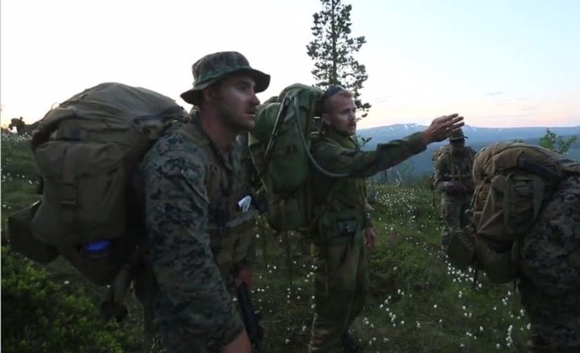 Screen shot of Marines on a mountain top discussing direction.
