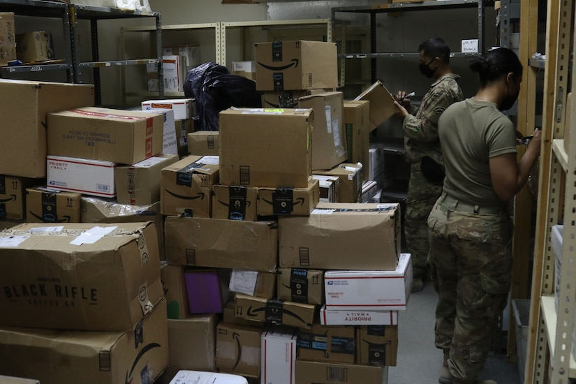 Soldiers work in a mailroom.
