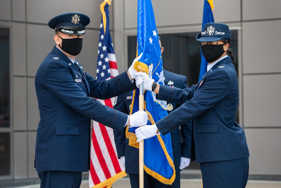 Col. James Smith, 50th Space Wing commander, left, passes the 50th Mission Support Group guidon to Col. Ericka Farmer-Hill, incoming 50th MSG commander, during a change of command ceremony July 7, 2020, at Schriever Air Force Base, Colorado. Farmer-Hill arrives at Schriever after serving as the Space and Missile Systems Center director of financial management and comptroller at Los Angeles AFB, California. (U.S. Air Force photo by Kathryn Damon)
