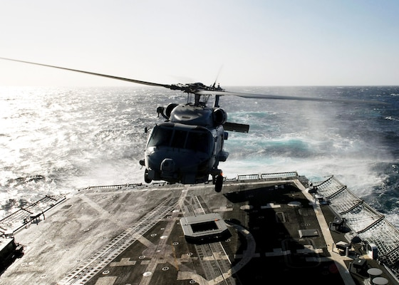 An SH-60B Sea Hawk Helicopter takes off from the flight deck of the guided missile frigate USS Preble (DDG 88). A carriage and tracks for the ship's recovery assistance, securing and traversing (RAST) system are on the deck below the helicopter.