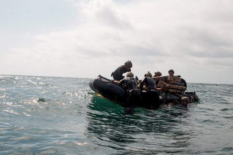 Marines in wet suits sit or swim around a rubber boat.